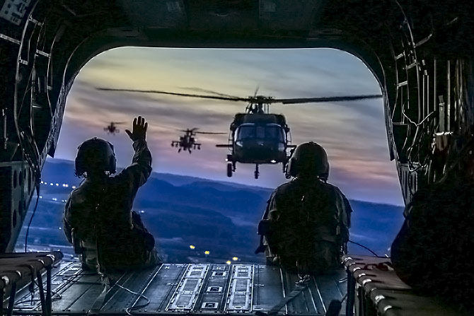 Two soldiers waving from plane to a helicopter